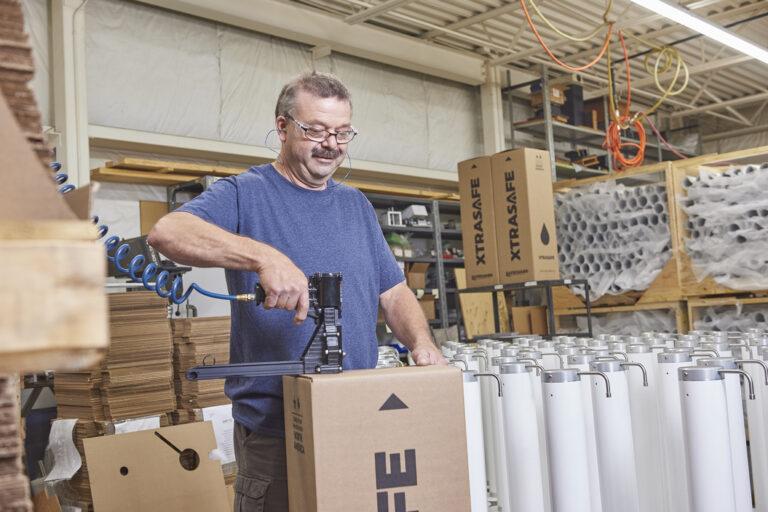Engineer packaging XtraSafe Sanitizer Dispenser in box