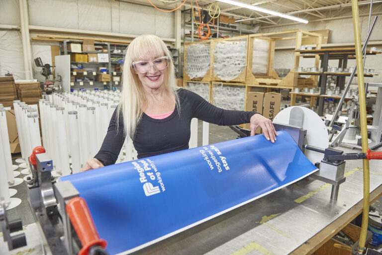 Engineer applying custom wrap to XtraSafe Sanitizer Dispenser